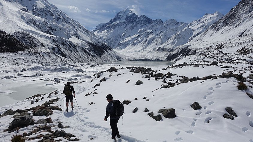 Two people walking through a snowy valley on the Hooker Valley Hike